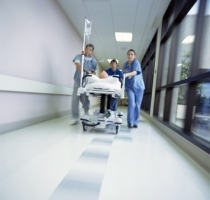 Doctors in scrubs rushing with patient on hospital gurney throug